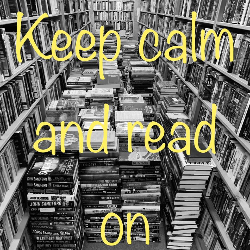Keep calm and read on displayed over large stacks of books